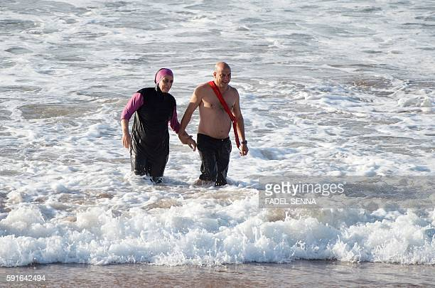 A Moroccan woman wearing a 'burkini' a fullbody swimsuit designed for Muslim women walks in the sea at Oued Charrat beach near the capital Rabat on...