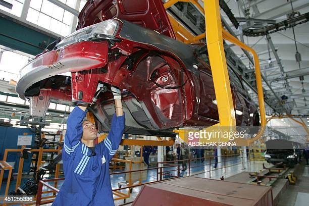 A Moroccan worker checks a Logan at the production line during the release of the 2000th Logan a bargain price car manufactured by Moroccan auto...