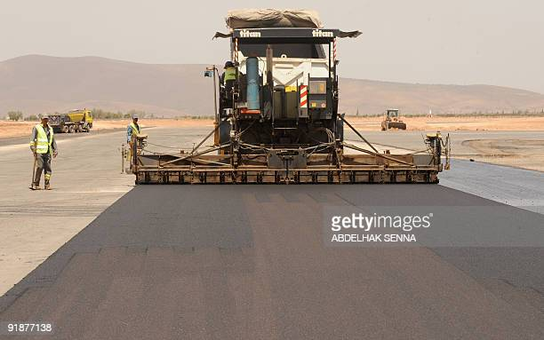 A Moroccan worker drives a Caterpillar asphalt screed at construction site on July 21 of Oujda airport French Colas and Moroccan GTR consortium won a...