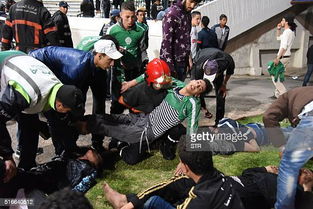 Moroccan youths lie on the pitch of the the Mohammed V stadium in Casablanca on March 19 following clashes between rival fans of Raja de Casablanca...