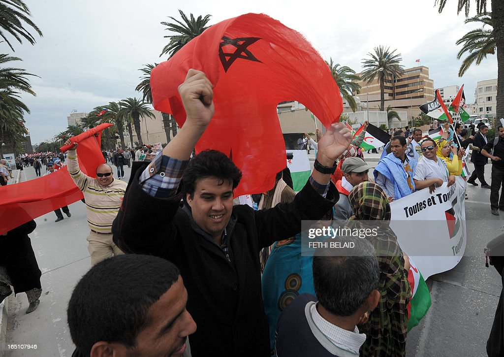 Moroccans wave their national flags near supporters of the Polisario Front separatist movement holding a banner reading 'All for Palestine, all for Western Sahara' during a demonstration at the closing of the World Social Forum (WSF) on March 30, 2013 in Tunis. AFP PHOTO / FETHI BELAID