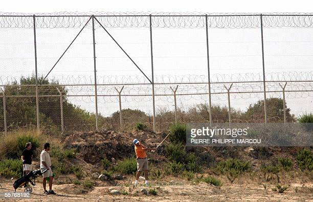 A group of men play golf by the fence which separates the Spanish enclave of Melilla from Morocco 25 September 2005 Spain has decided to double the...