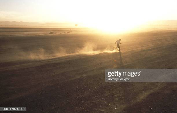 Morocco, Draa Valley, man running through sandstorm
