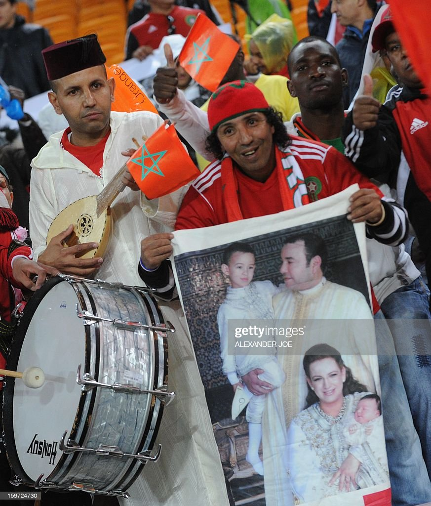 Morocco fans smile and hold a poster of the Moroccan Royal family at the start of their match against Angola during the 2013 African Cup of Nations at Soccer City in Soweto on January 19, 2013.