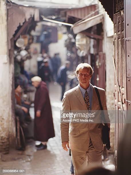 Morocco, Fez, businessman walking through Medina Market