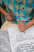 Morocco, Fez, man carving Arabic script in marble, mid section