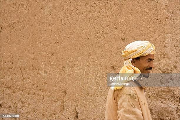 Morocco: Man in Turban Walking Past Mud/Adobe Wall