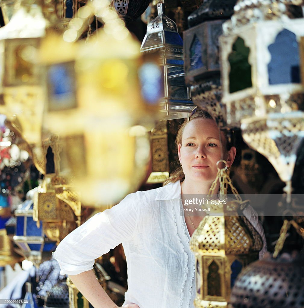 Morocco, Marrakesh, woman looking at silverware (focus on woman) : Stock Photo