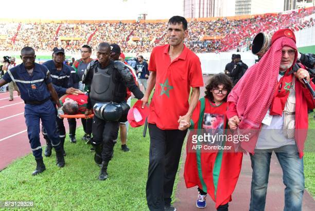 A Morocco team supporter suffering from heat exhaustion is stretchered to a medical tent as a child is escorted too at the Felix HouphouetBoigny...