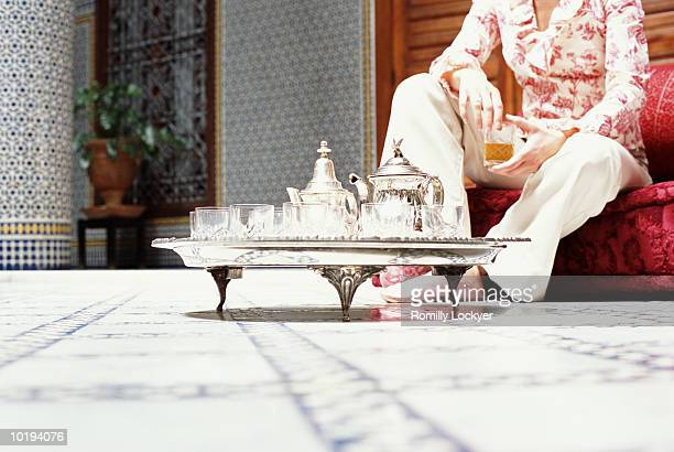 Morocco, woman drinking mint tea, low section