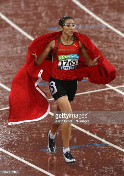 Morocco's Sanaa Benhama celebrates with her National flag after winning the Women's 100m T13 Final in the National Stadium in Beijing China