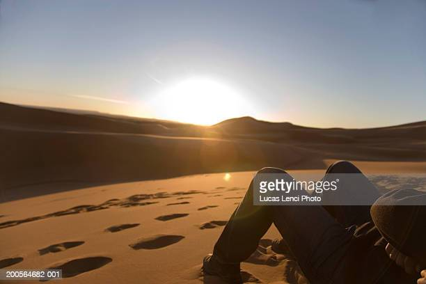 Morocco,Sahara desert, man laying on sand dunes facing sunrise