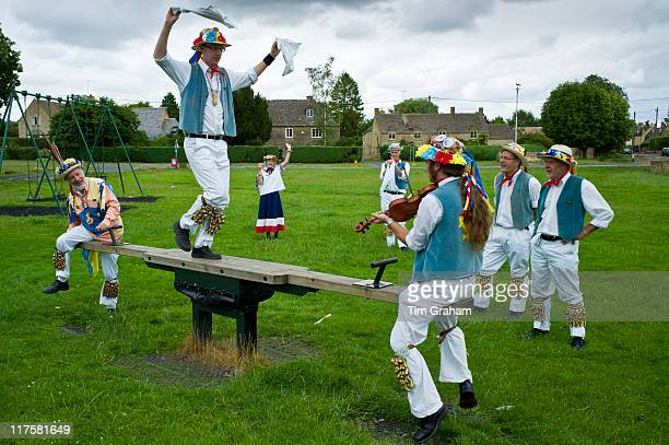 Morris dancers Icknield Way Morris Men in children's playground at The Kings Head Pub Bledington Oxfordshire UK