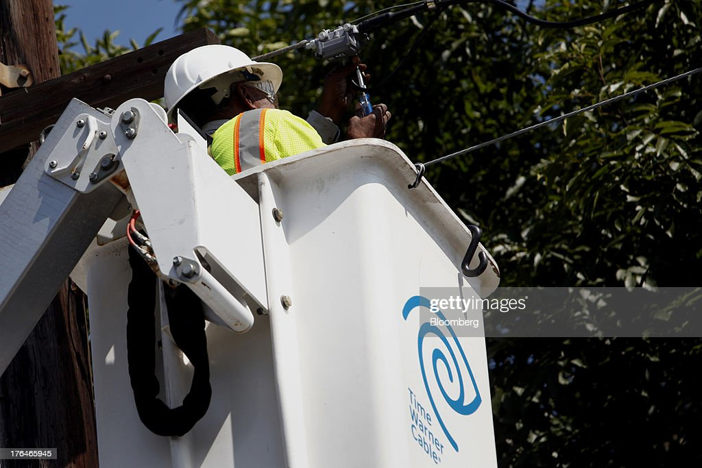 Morris Hibbitt, a field technician for Time Warner Cable, cleans and checks the connection for a WiFi hotspot using a bucket truck in Manhattan Beach, California, U.S., on Monday, Aug. 12, 2013. Time Warner Cable Inc. said it's talking with CBS Corp., after a breakdown in negotiations led the cable provider to block its customers from seeing the network. Photographer: Patrick Fallon/Bloomberg via Getty Images