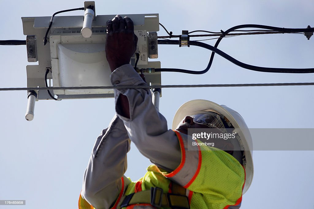 Morris Hibbitt, a field technician for Time Warner Cable, cleans and checks the connection for a WiFi hotspot using a bucket truck in Manhattan Beach, California, U.S., on Monday, Aug. 12, 2013. Time Warner Inc., owner of the TNT, CNN and HBO cable channels, reported second-quarter profit that topped analysts estimates, boosted by higher advertising revenue. Photographer: Patrick Fallon/Bloomberg via Getty Images