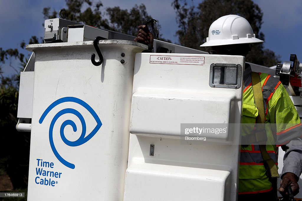 Morris Hibbitt, a field technician for Time Warner Cable Inc., cleans and checks the connection for a WiFi hotspot using a bucket truck in Manhattan Beach, California, U.S., on Monday, Aug. 12, 2013. Time Warner Cable Inc. said it's talking with CBS Corp., after a breakdown in negotiations led the cable provider to block its customers from seeing the network. Photographer: Patrick Fallon/Bloomberg via Getty Images