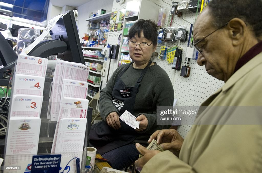 Morris James of Washington, DC, purchases Powerball lottery tickets for the estimated record 425 million USD jackpot prize, Powerball's biggest winnings ever, from convenience store clerk Amy Suh (C) at the Vermont Convenience store in Washington on November 26, 2012. The previous drawing resulted in no winner, setting up for the record setting prize when numbers will be drawn on Wednesday. Tickets are sold in 42 US states, Washington, DC, and the US Virgin Islands. AFP PHOTO / Saul LOEB
