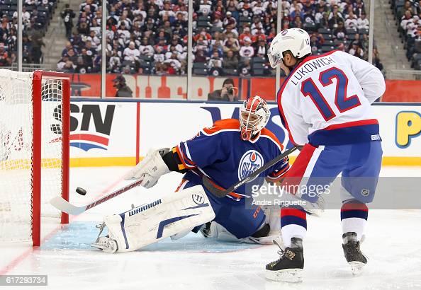 Morris Lukowich of the Winnipeg Jets alumni fires a shot on Dwayne Roloson of the Edmonton Oilers alumni during the 2016 Tim Hortons NHL Heritage...