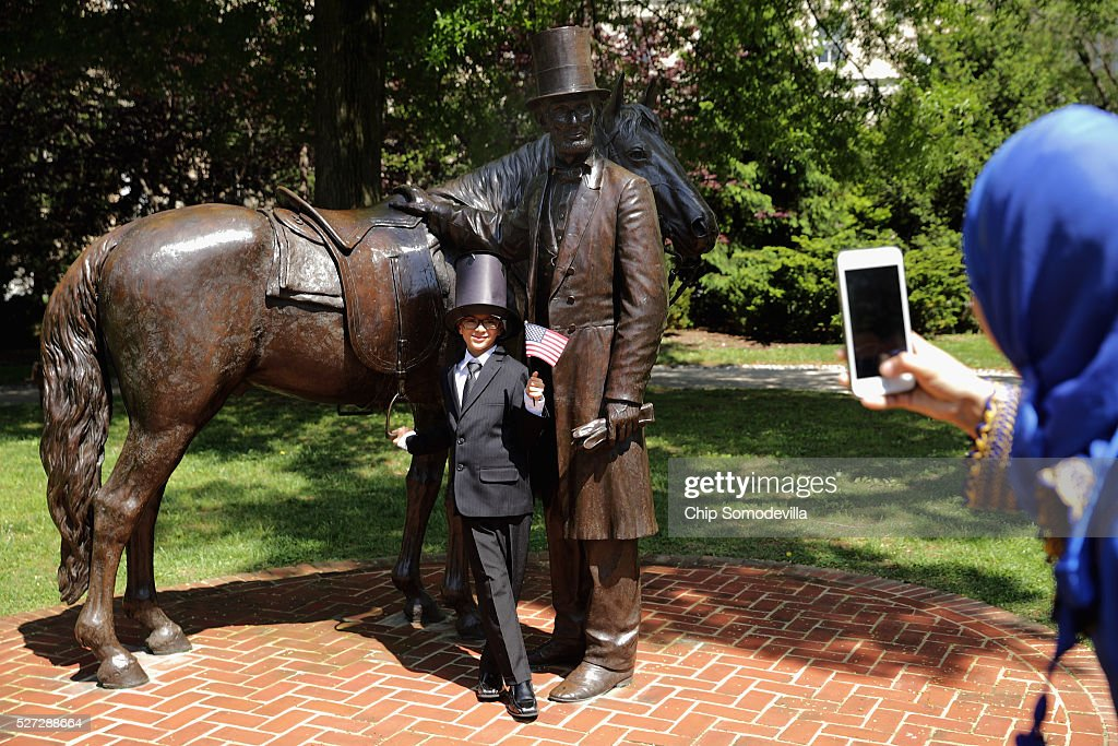 Morrocan native Yahya Ahmed Aflal, 6, has his photograph taken with a statue of President Abraham Lincoln following a childrens citizenship ceremony at President Lincoln's Cottage at the Soldiers' Home May 2, 2016 in Washington, DC. Twenty one children from 19 countries, including Syria, South Korea and El Salvador, became new United States citizens during the ceremony sponsored by the U.S. Citizenship and Immigration Services. President Abraham Lincoln and his family resided seasonally on the grounds of the Soldiers' Home to escape the heat and politics of downtown Washington, as did President James Buchanan before him and presidents Rutherford B. Hayes and Chester A. Arthur from 1885 to 1887.