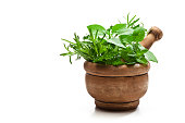 Front view of an old wooden mortar filled with fresh organic herbs for cooking shot on white background. The mortar is at the right of an horizontal frame leaving useful copy space for text and/or log