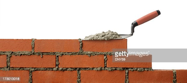 Mortar on trowel sitting on unfinished brick wall