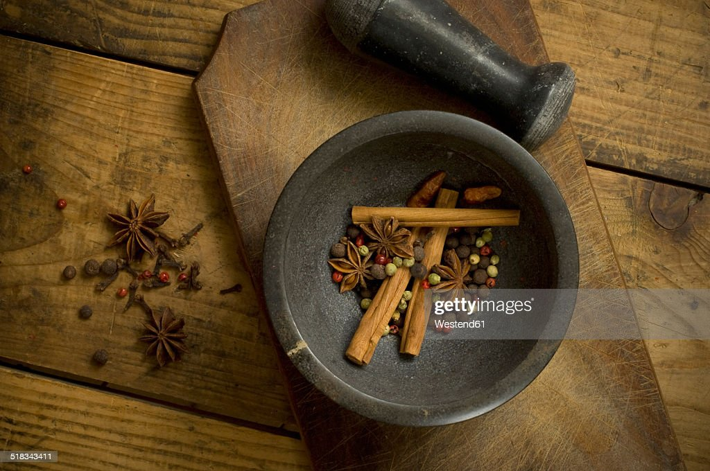 Mortar with dried peppercorns, star anise and cinnamon sticks on wood, elevated view