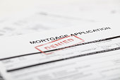 """A stock photo of a Mortgage application form with a red """"denied"""" stamp"""