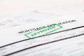 """A stock photo of a Mortgage application form with a green """"approved"""" ink stamp"""