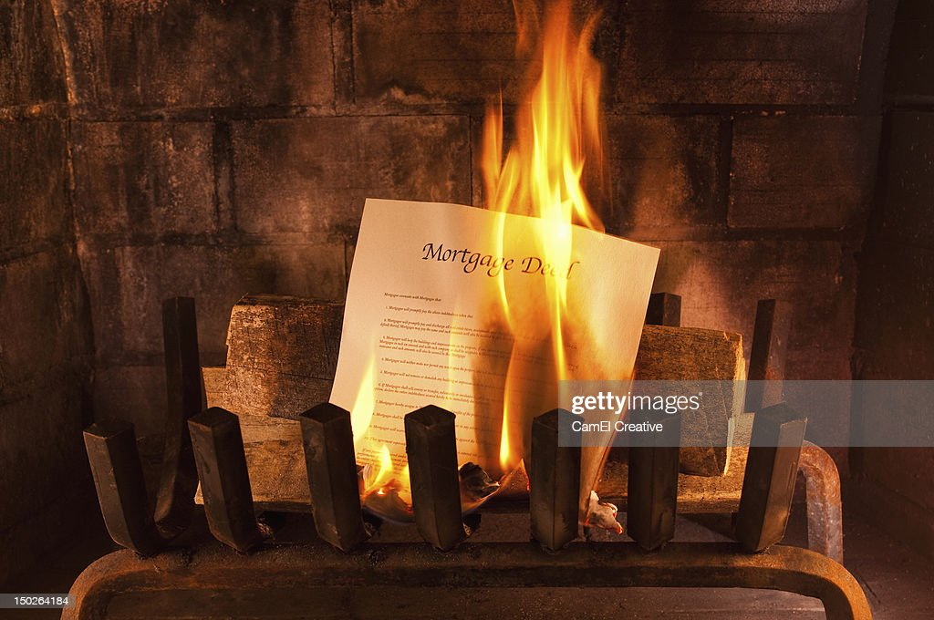 A mortgage deed burning in a fireplace : Stock Photo