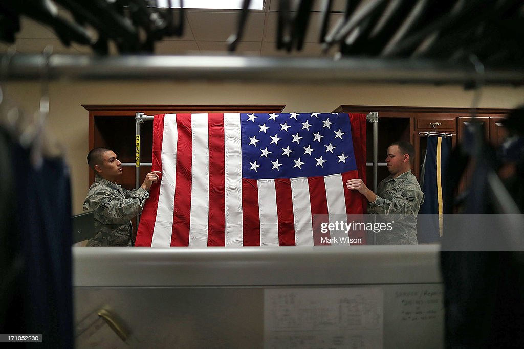 Mortuary Technicians U.S. Air Force 1st Class Cody Rodriguez (L) and U.S. Air Force Senior Airman Christopher Cox press the wrinkles from a flag in the uniform preparation shop at Dover Air Force Base, June 21, 2013 in Dover, Delaware. Since the 1950s fallen members of the military fighting in conflicts aboard are brought to Dover's Air Force Mortuary Affairs operations complex which is the Defense Departments largest joint service mortuary facility in the United States.