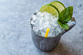 Moscow Mule Cocktail with Lime, Mint Leaves and Crushed Ice in Metal Cup. Summer Beverage.