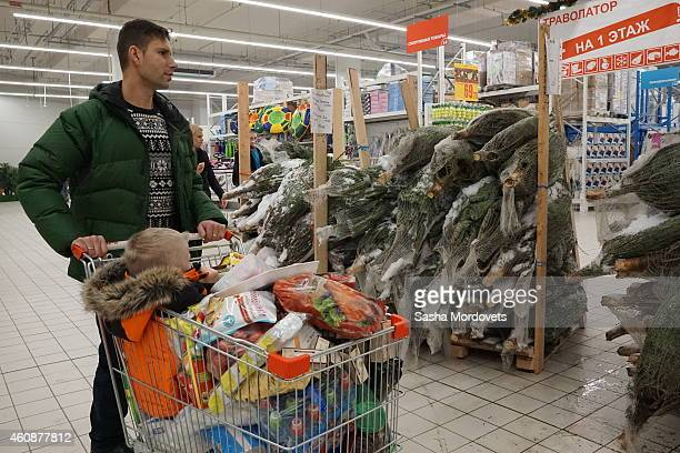 Moscow residents buy goods in the Auchan store on December 28 2014 in Moscow Russia The Russian currency crashed to historic lows against the US...