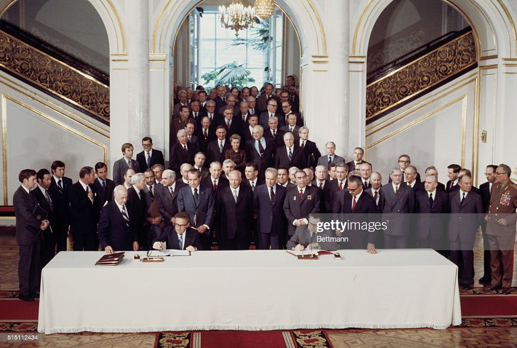 With President Nixon watching over his shoulder U S Secretary of State Henry Kissinger puts his signature to one of two secret documents at signing...