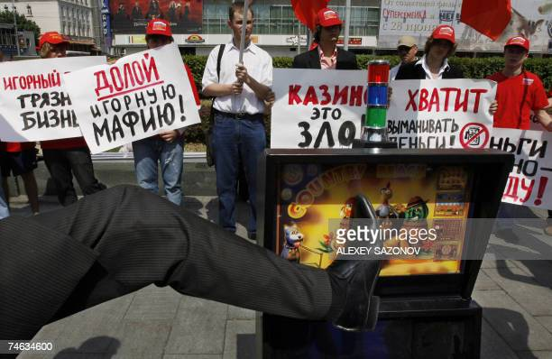 An activist of the Hurrah youth movement of the Russia of Justice party kicks a gambling machine 15 June 2007as his peers hold flags and posters...