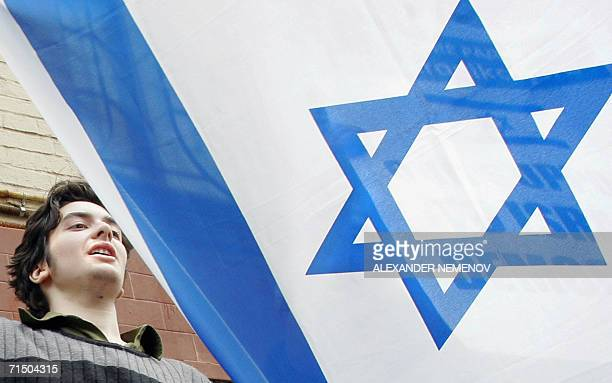 An activist waves an Israeli flag outside Israel's embassy in Moscow to voice support for the current Israeli military action in Lebanon 23 July 2006...