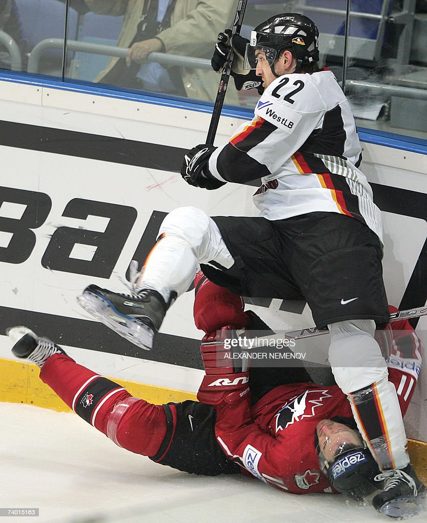 Germany's Michael Bakos fights for the puck with Canada's Justin Williams during their preliminary round group C game of the IIHF International Ice...