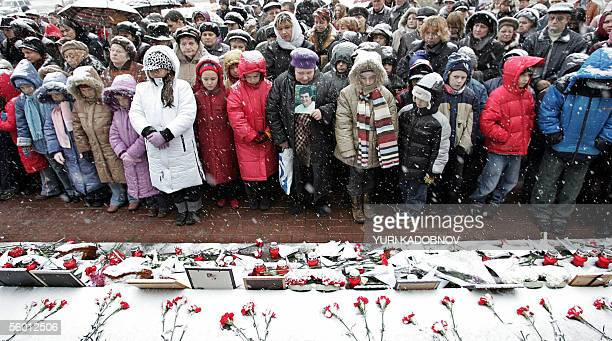 People stand in front of the Dubrovka Theatre during a commemoration ceremony in Moscow 26 October 2005 where Chechen commandos took hundreds of...