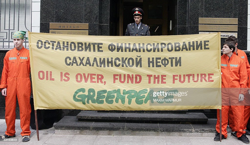Russian Greenpeace activists hold a banner reading 'Stop the financing of Sakhalin oil' 27 June 2005 during their protest in front of the Moscow...