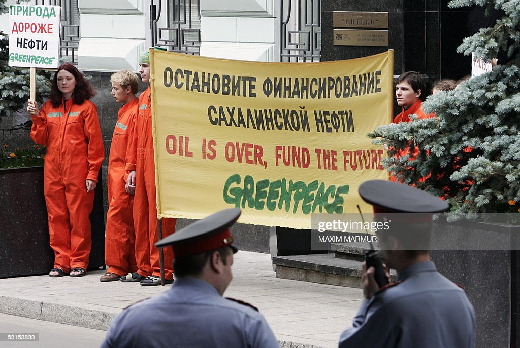 Russian police watch Russian Greenpeace activists holding a banner reading 'Stop the financing of Sakhalin oil' 27 June 2005 during their protest in...