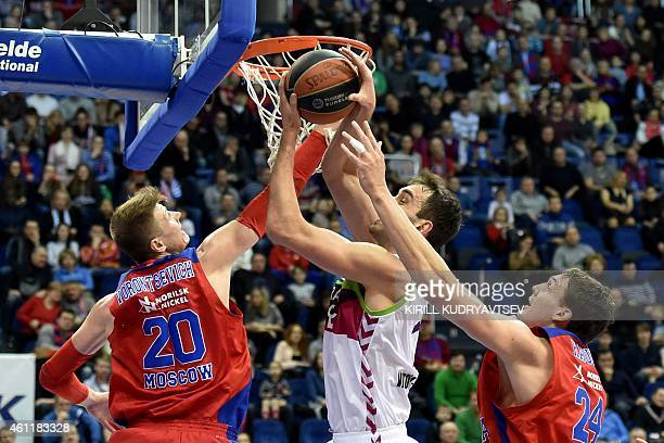 Moscow's players Andrey Vorontsevich and Sasha Kaun fight for the ball with Laboral Kutxa Vitoria's player Mirza Begic during their Euroleague Top16...