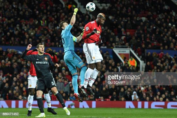 Moscow's Russian goalkeeper Igor Akinfeev punches clear under pressure from Manchester United's French midfielder Paul Pogba during the UEFA...