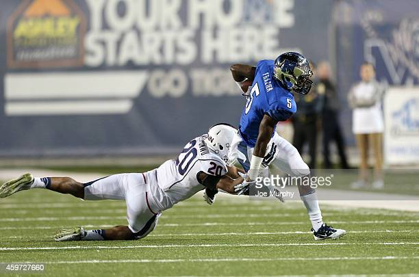 Mose Frazier of the Memphis Tigers breaks a tackle from Obi Melifonwu of the Connecticut Huskies on November 29 2014 at Liberty Bowl Memorial Stadium...