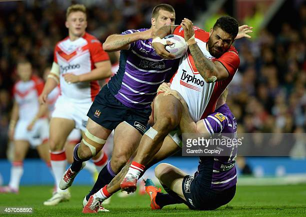 Mose Masoe of St Helens is tackled by Blake Green and Liam Farrell of Wigan Warriors during the First Utility Super League Grand Final between St...