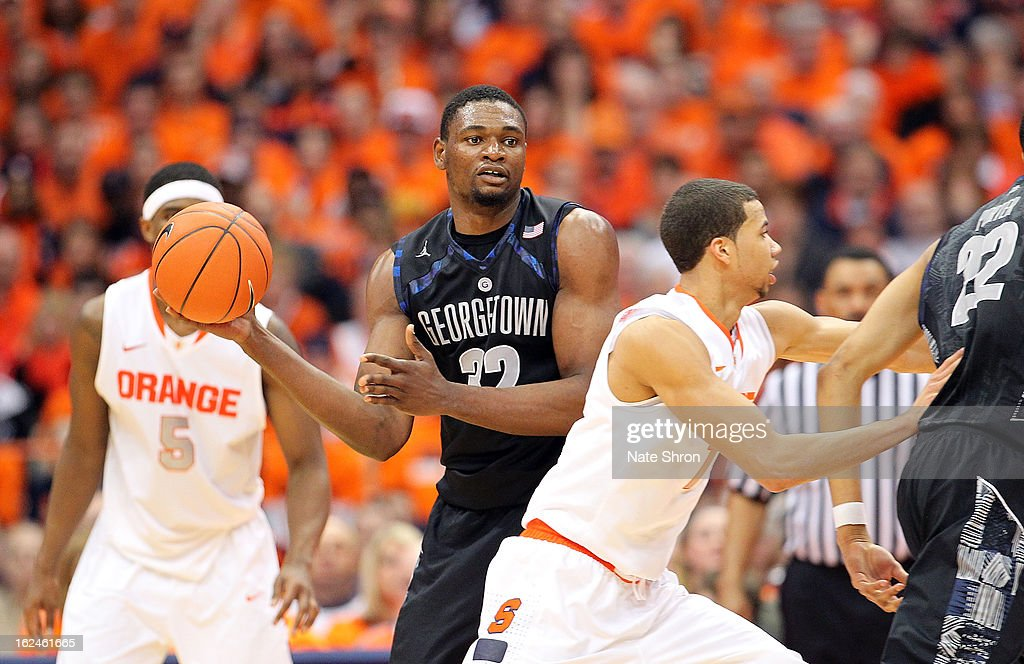 Moses Ayegba #32 of the Georgetown Hoyas passes the ball against C.J. Fair #5 and Michael Carter-Williams #1 of the Syracuse Orange during the game at the Carrier Dome on February 23, 2013 in Syracuse, New York.