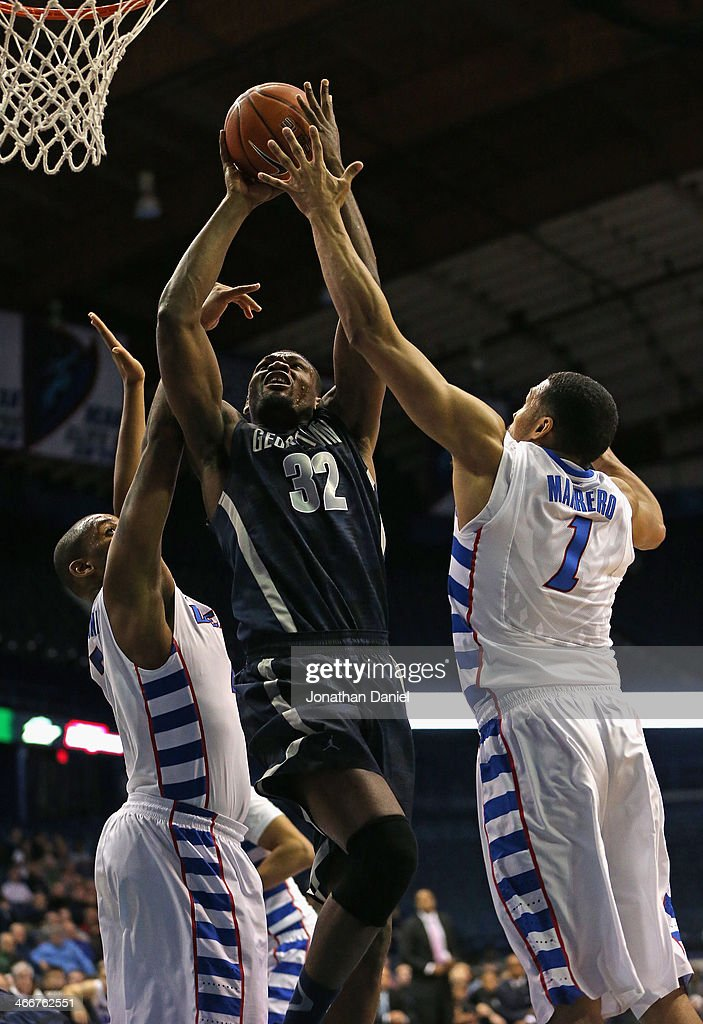 Moses Ayegba #32 of the Georgetown Hoyas shoots between Tommy Hamoltin IV #2 (L) and DeJuan Marrero #1 of the DePaul Blue Demons at the Allstate Arena on February 3, 2014 in Rosemont, Illinois.