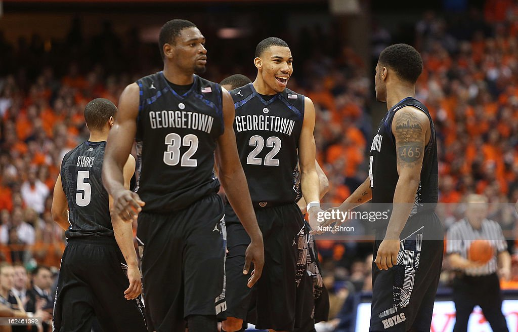 Moses Ayegba #32, Otto Porter Jr. #22 and D'Vauntes Smith-Rivera #4 of the Georgetown Hoyas celebrate their win over the Syracuse Orange during the game at the Carrier Dome on February 23, 2013 in Syracuse, New York.