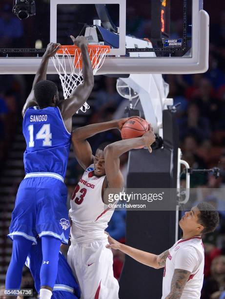 Moses Kingsley of the University of Arkansas pulls down an intercepted pass as Ismael Sanogo of Seton Hall University hits the rim after attempting...