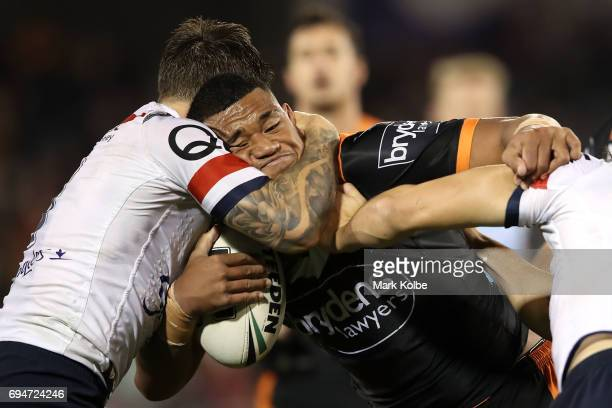 Moses Suli of the Tigers is tackled by Mitchell Pearce and Aidan Guerra of the Roosters during the round 14 NRL match between between the Wests...
