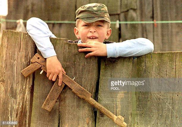 Moslem boy holding a toy gun 03 May peers over a fence as a British army patrol passes through his neighborhood Fighting between Moslem and Croat...