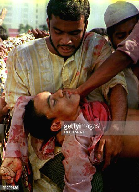 Moslem carries an injured friend who was hurt during protests 07 December 1992 against the destruction by Hindus of the mosque in Ayodhya India Over...